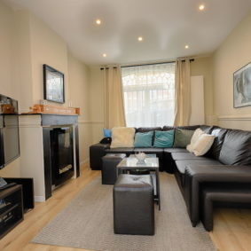 stylish living room in the abdication house with big screen television and comfortable black sofas