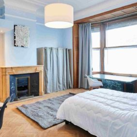 comfortable room with double bed and a private shower for a tenant in a shared house