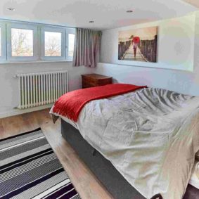 room with double bed designed with style and with a private shower in a coliving space for expats