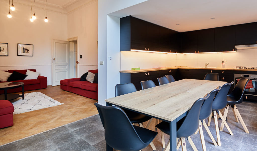 fully equipped kitchen designed in black with a big dining table in a shared house for expats in Brussels