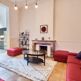 well designed living room with stylish red sofas in a shared house for expats in Brussels