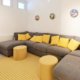 cosy chilling room with comfortable grey sofas in a shared house for 9 young professionals close to the European Commission