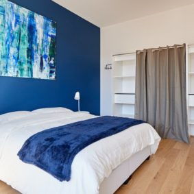 room with a comfortable double bed decorated in the blue style with a private shower in a shared house for expats in Brussels