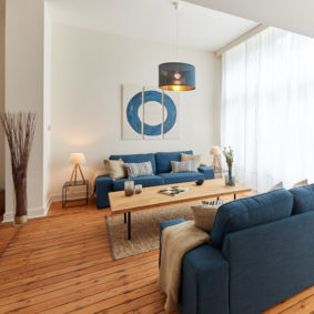 well designed living room with stylish blue sofass in a shared house for young professionals in Brussels