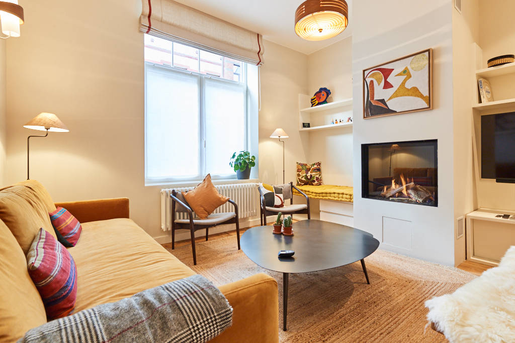 living room in a coliving mansion decorated with taste with an open fire and a large screen TV with Netflix