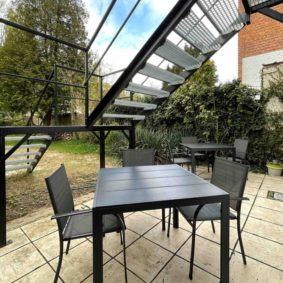 Furnished terrace with chairs and tables and a BBQ to enjoy with your housemates in a spacious garden in a shared house in Brussels